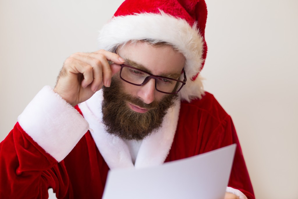 Focused guy wearing Santa costume and reading document. Bearded man working. Christmas and business concept. Front view.
